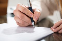 Business Person Signing Document With Pen. Close-up Of A Business Person Signing Document With Pen On The Desk royalty free stock photography