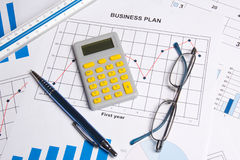 Close up of business plan with graphs, charts, glasses and calcu Stock Image