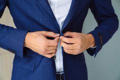 Close-up business stylish man buttoning his blue jacket, standing in a stylish office with designer repair. Close-up business stylish man buttoning his blue stock image