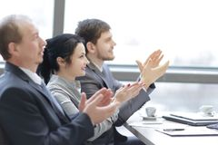Close up.business team applauding the speaker, sitting in the workplace. royalty free stock photography