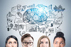 Close up of business team, brain and gears. Close up of a group of young business people standing near a gray wall with a brain and gears sketch and a startup Royalty Free Stock Image