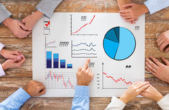 Close up of business team with charts at table. Business, people, statistics and team work concept - close up of creative team sitting at table and pointing Royalty Free Stock Images