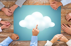 Close up of business team hands with cloud picture. Business, people and team work concept - close up of creative team hands at table pointing finger to cloud royalty free stock image