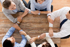 Close up of business team holding hands at table Royalty Free Stock Photo