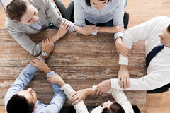 Close up of business team holding hands at table Stock Image