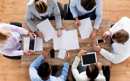 Close up of business team with papers and gadgets. Business, people and team work concept - close up of creative team with papers and gadgets meeting in office royalty free stock image