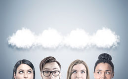 Close up of a business team, thought clouds. Close up of members of a business team s heads. They are standing near a gray wall with thought clouds above them Stock Image