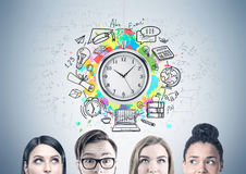 Close up of a business team, time management. Members of a diverse business team are standing near a gray wall and thinking. There is a clock and a time stock images