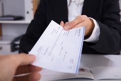 Business Woman Handing Over Cheque To Her Colleague royalty free stock image