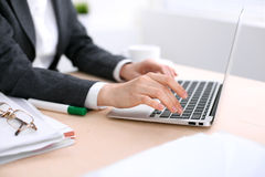 Close up of business woman hands typing on laptop computer in the white colored office Stock Image