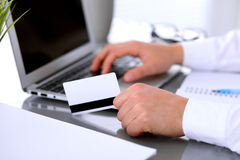 Close up of business woman hands using credit card and laptop computer Stock Photography