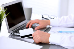 Close up of business woman hands using credit card and laptop computer Royalty Free Stock Photos