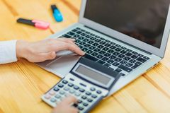 Close up of business woman holding hands with black calculator and laptop while sitting at desk in office background. royalty free stock photos