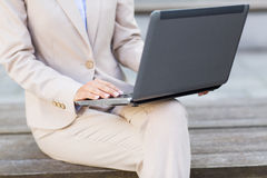 Close up of business woman with laptop in city Stock Photography