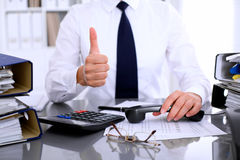 Close up of business woman showing ok sign while making report, calculating or checking balance. Stock Images