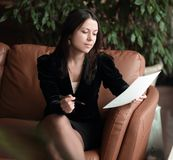 Close up. business woman sitting in business center and reading documents royalty free stock image