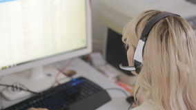 Close-up of business woman talking on headset in a call center stock video footage