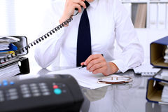 Close up of business woman talking by phone  while making report, calculating or checking balance. Stock Photography