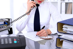 Close up of business woman talking by phone  while making report, calculating or checking balance. Royalty Free Stock Photography