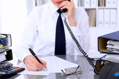 Close up of business woman talking by phone  while making report, calculating or checking balance. Stock Image