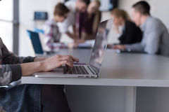 Close up of business womans hand typing on laptop with team on m Stock Photos