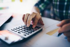 Close up of businessman or accountant working on calculator to calculate business data, and accountancy document. Business. Financial and accounting concept stock photography