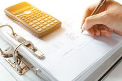 Close-up of a Businessman Analyzing Writing note accounting docu. Ment with calculator at desk in office. soft focus Stock Photo