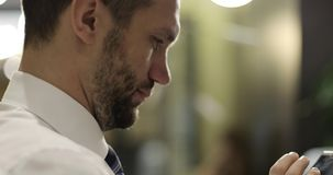 Close up of businessman bearded face and hands typing on mobile phone. Stylish man in white shirt and tie is using tablet stock video footage
