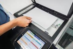 Businessman in blue shirt put paper sheet onto printer scanning Stock Images