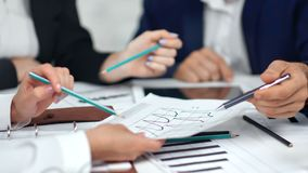 Close-up businessman and businesswoman hand holding pen and pencil pointing on paper graphic. With data on desk. Business people having brainstorming during stock footage