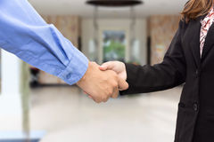 Close up of businessman and businesswoman shaking hands in waiti Royalty Free Stock Photos