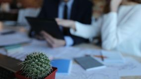 Close-up businessman and businesswoman with tablet in the office. Two close-up businesspeople sit and have meeting, discussing report and using digital tablet stock video footage