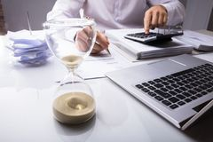 Businessman Calculating Invoice With Hourglass. Close-up Of Businessman Calculating Invoice With Hourglass And Laptop On Desk In Office stock images