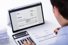 Businessman Calculating The Invoice. Close-up Of Businessman Calculating The Invoice Using Hybrid Laptop And Calculator At Workplace royalty free stock image