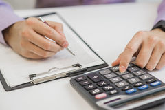 Close-up Of Businessman Calculating Invoices Using Calculator.  Royalty Free Stock Photography