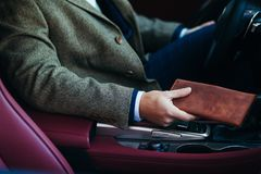 Close up of the businessman in the car with a purse Royalty Free Stock Photography