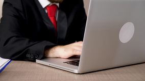 Close up businessman checking papers with diagrams and then typing on computer. Dolly footage stock footage