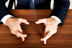 Close up of businessman cross fingers on the desk Royalty Free Stock Image