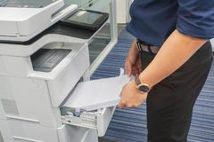 Businessman in dark blue shirt insert A4 paper sheet into office printer tray. Close up businessman in dark blue shirt insert A4 paper sheet into office printer stock photo