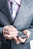 Close-up of a businessman in dark gray suit. Close-up of a businessman holding pocket PC, focus on hand Royalty Free Stock Photos