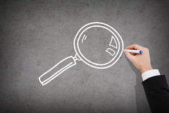 Close up of businessman drawing magnifying glass Stock Images