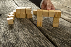 Close up of businessman forming a bridge of small wooden blocks Royalty Free Stock Photos