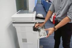 Businessman in grey shirt open the toner cartridge for inkjet printer royalty free stock image