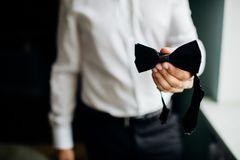Close-up businessman groom holding bow-tie in his hands. Concept royalty free stock image