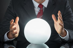 Close-up Of Businessman Hand On Crystal Ball. On Desk Stock Photo