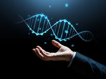 Close up of businessman hand with dna molecule. Business, science, genetics and people concept - close up of businessman hand with dna molecule projection over stock images
