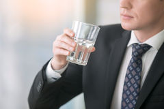 Close up of businessman hand with a glass of water Royalty Free Stock Image