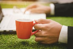 Businessman hand holding coffee  cup and using laptop o. Close up businessman hand holding coffee cup and using laptop on green grass Royalty Free Stock Photos