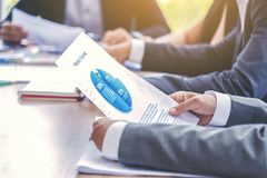 Close up on businessman hand holding paper a graph of yearly sales while having a management meeting of annual company meeting.  royalty free stock photos