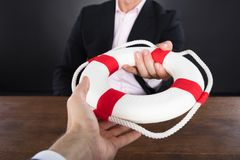 Businessman Passing A Lifebuoy To A Partner Stock Photography
